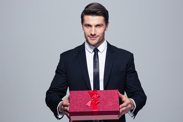 Handsome businessman holding gift box over gray background and looking at camera