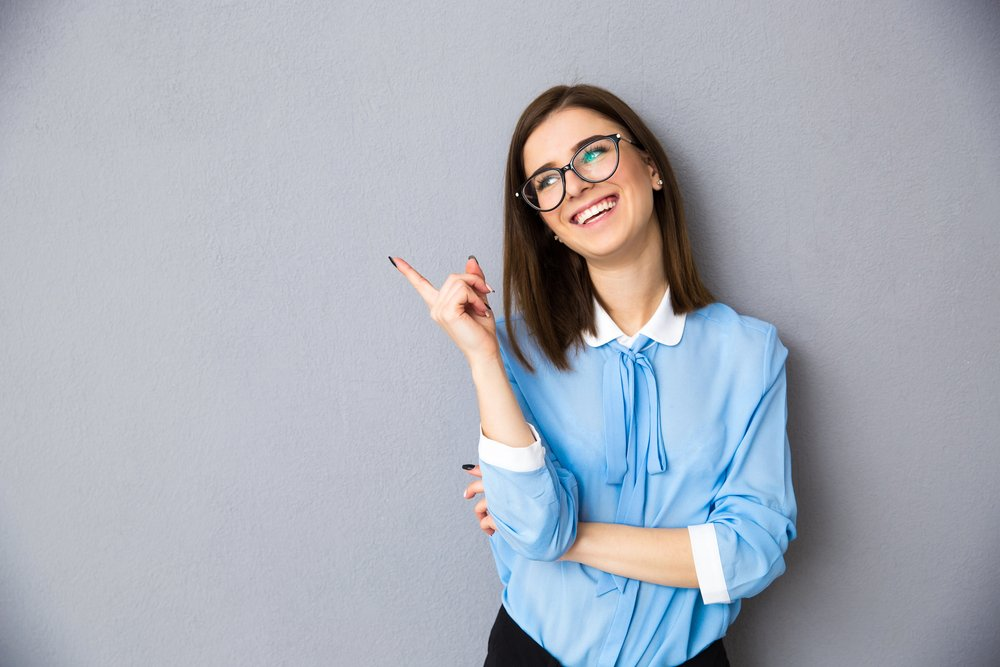 Cheerful businesswoman pointing away over gray background. Wearing in blue shirt and glasses. Looking away