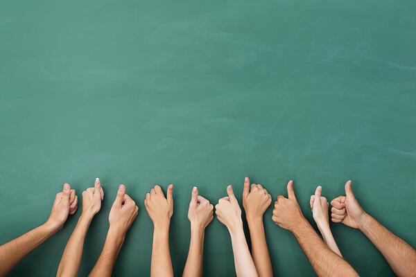 Close up view of the hands of a group of people giving a thumbs up gesture of approval an success with their hands raised against a blank green chalkboard with copyspace