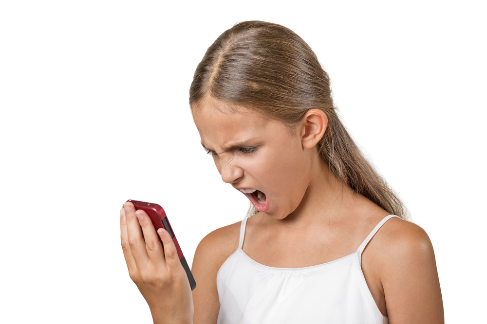 Closeup portrait young mad, frustrated angry teenager girl yelling while on phone isolated white background. Negative human emotion facial expression feelings. Communication, conflict resolution