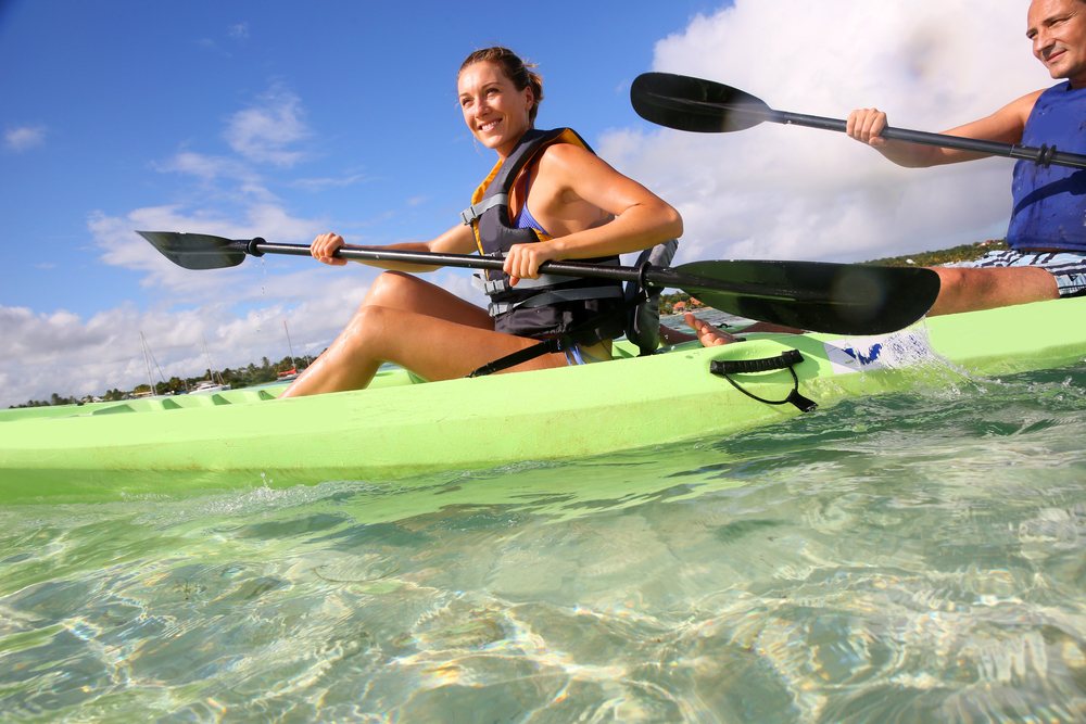 Couple canoeing in lagoon of West French indies-1