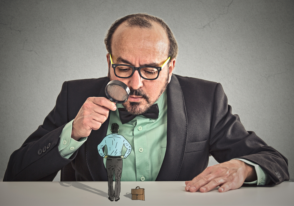 Curious corporate businessman skeptically meeting looking at small employee standing on table through magnifying glass isolated office grey wall background. Human face expression, attitude, perception-2