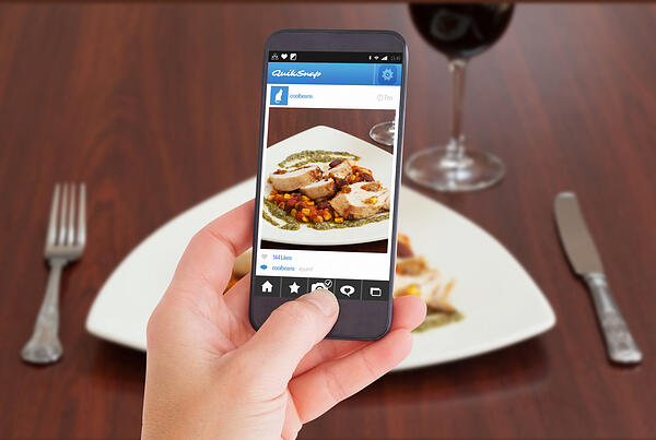 Female hand holding a smartphone against high angle view of delicious chicken dish with salsa