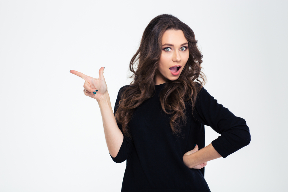 Portrait of a beautiful woman pointing finger away isolated on a white background