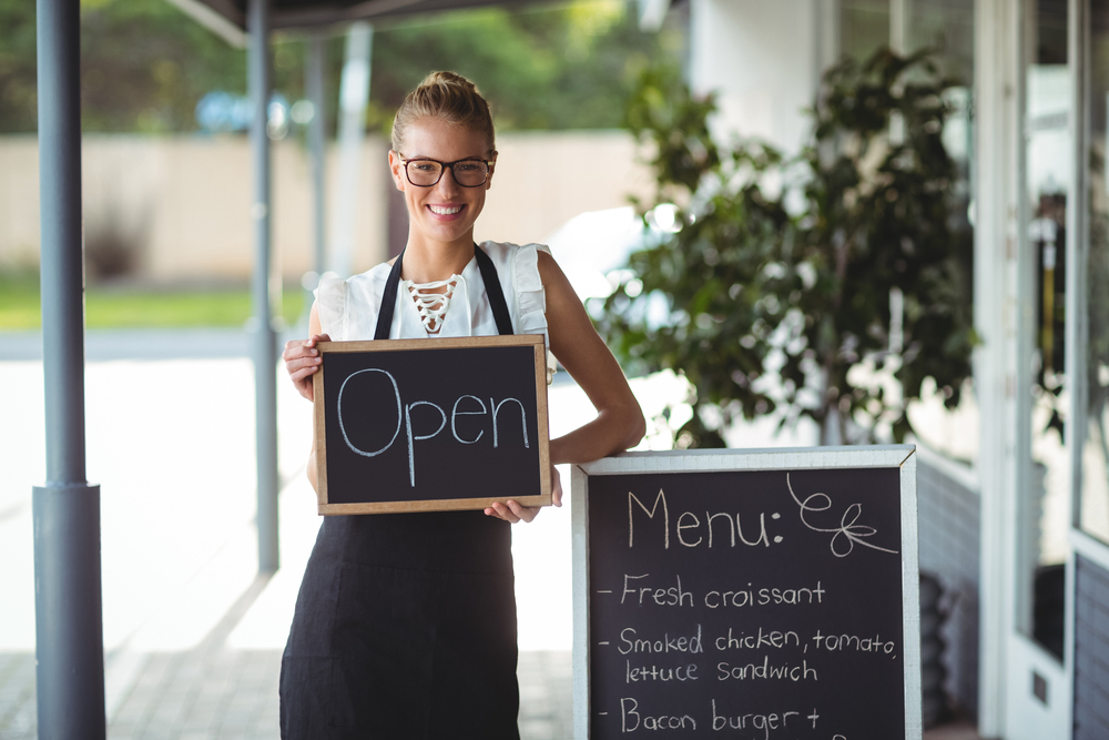 Portrait of waitress standing with chalkboard and menu outside the cafe