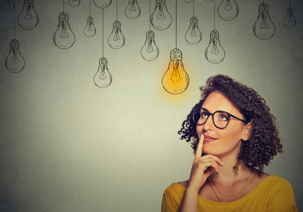 Thinking woman in glasses looking up with light idea bulb above head isolated on gray wall background-1