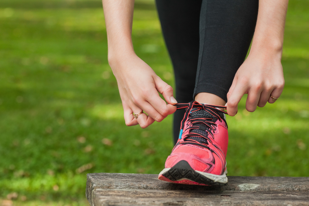 Young woman tying the shoelaces of her running shoes on a bench